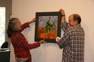 Bobby Blitzer and Roger Lazoff hang a painting by Ian Warpole
